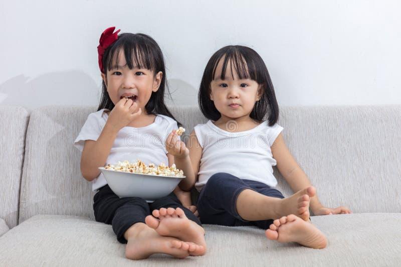 Lyckliga asiatiska kinesiska små systrar som äter popcorn på soffan royaltyfri bild