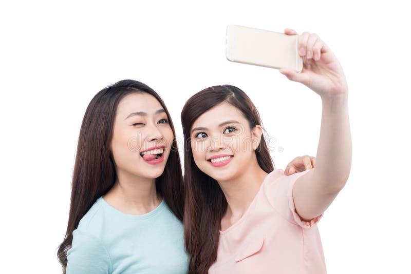 Lyckliga asiatiska kvinnavänner som tar en självstående med en cellpho fotografering för bildbyråer