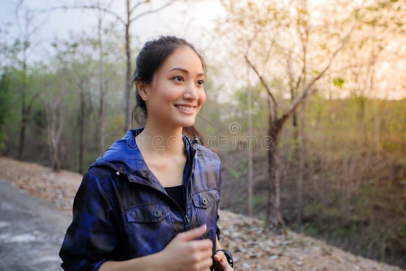 Lyckliga asiatiska kvinnor som ler och, medan jogga utanför på streen royaltyfria foton