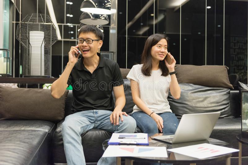 Lyckliga asiatiska par arbetar tillsammans och kallar på natten royaltyfri foto