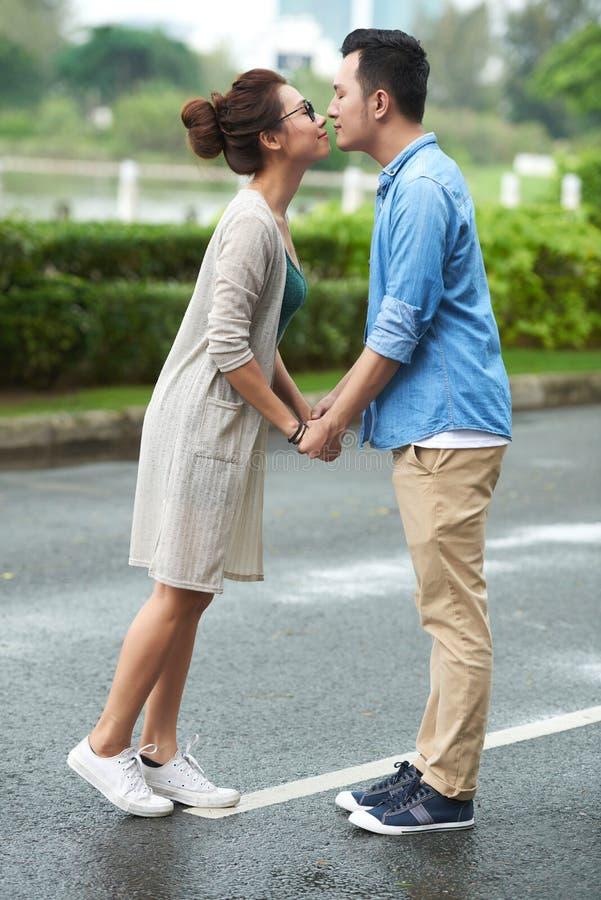 Lyckliga asiatiska par som försiktigt kysser på datum royaltyfri foto