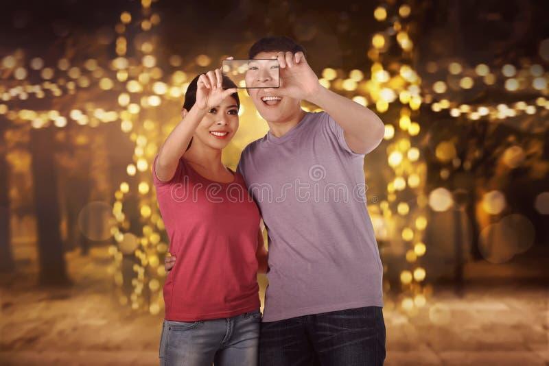 Lyckliga asiatiska par som gör selfie royaltyfria foton