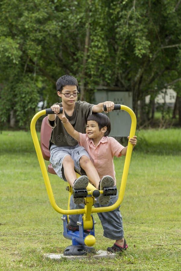 Lyckliga asiatiska pojkar som tillsammans spelar på lekplats royaltyfri foto