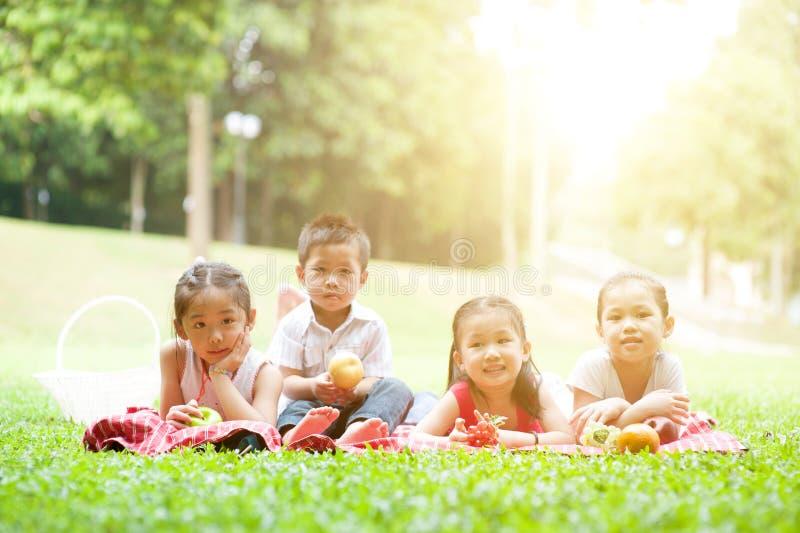 Lyckliga asiatiska utomhus- barnpicknickar arkivbilder