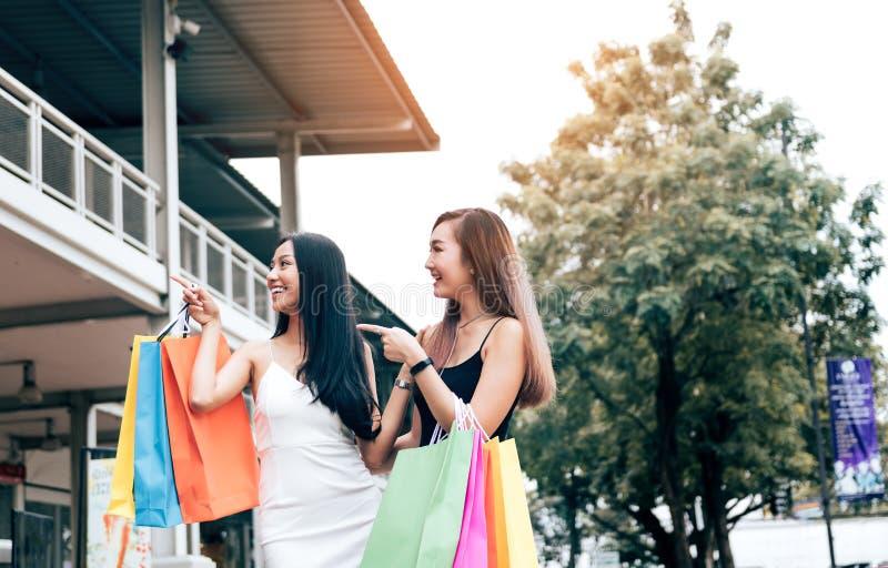 Lyckliga asiatiska vänner som går på gallerian med att göra shopping tillsammans arkivfoton