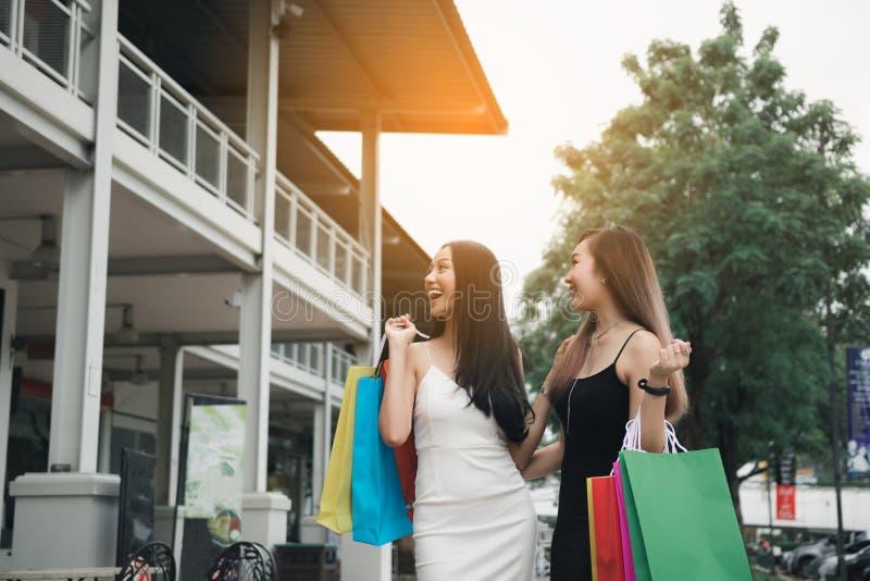 Lyckliga asiatiska v?nner som g?r p? gallerian med att g?ra shopping tillsammans arkivbild