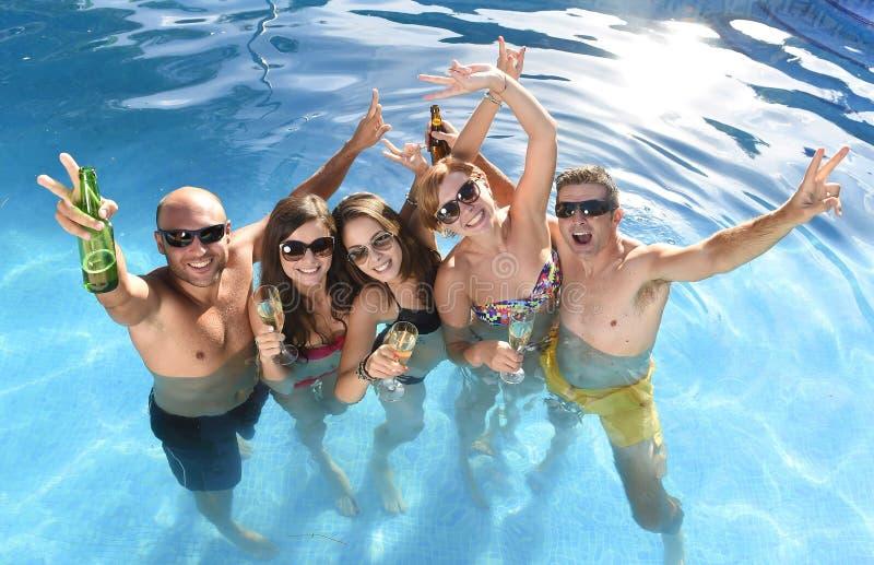 Lyckliga attraktiva män och kvinnor i bikinin som har badet på hotellsemesterortsimbassängen som dricker öl fotografering för bildbyråer