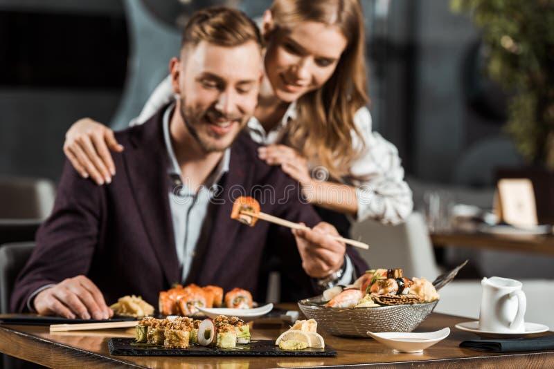 Lyckliga attraktiva par som har matställen och äter smakliga sushirullar arkivbild
