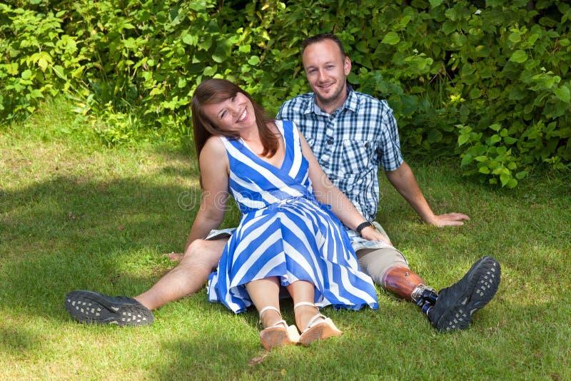 Lyckliga attraktiva par som kopplar av i trädgården arkivfoto