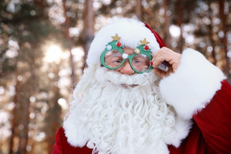 Lyckliga autentiska Santa Claus med roliga exponeringsglas utomhus arkivbild