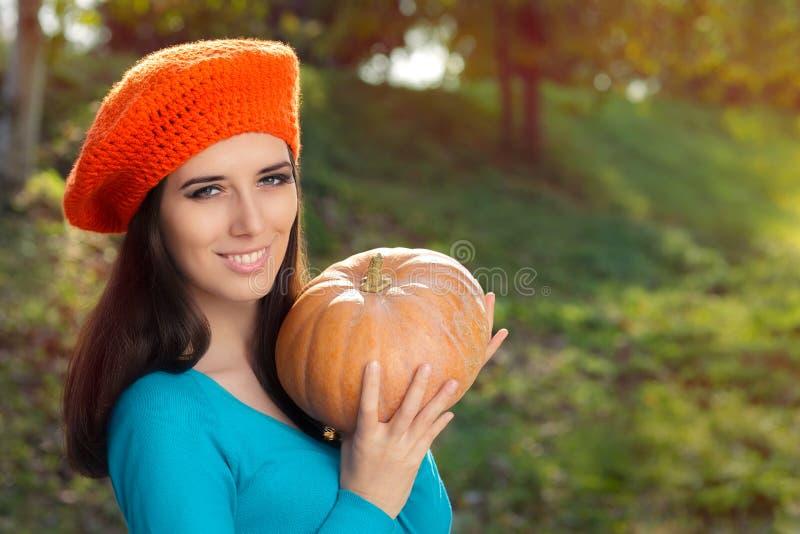 Lyckliga Autumn Woman Holding Pumpkin royaltyfria foton