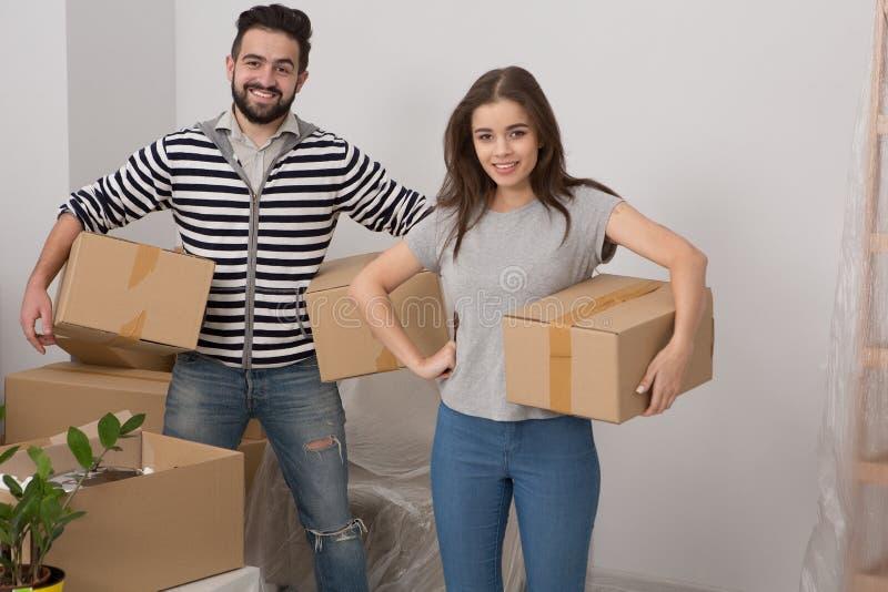 Lyckliga bärande askar för make och för fru i deras nya hus arkivfoton