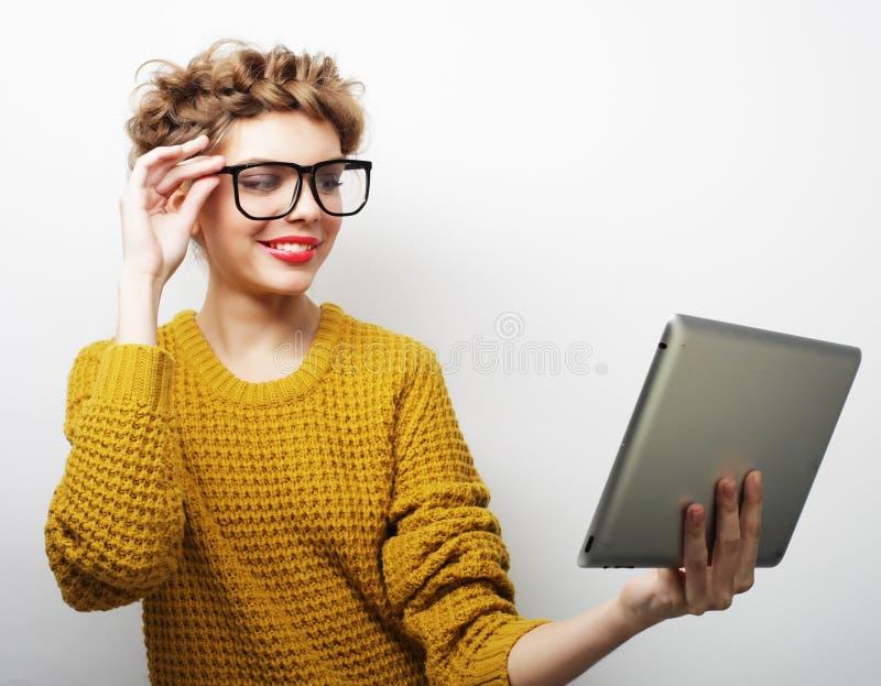 Lyckliga bärande exponeringsglas för tonårs- flicka med minnestavlaPCdatoren arkivfoton