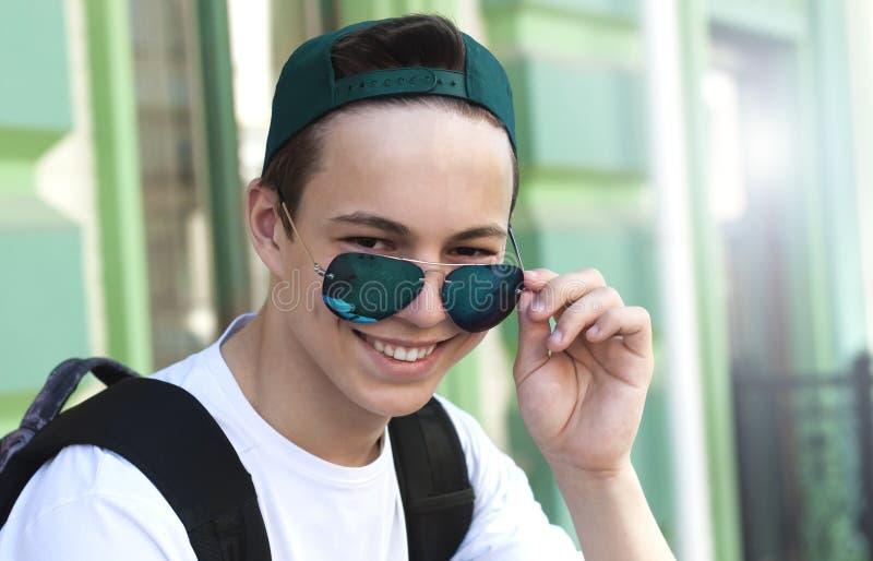 Lyckliga bärande exponeringsglas för ung man, på stadsgatan royaltyfria foton