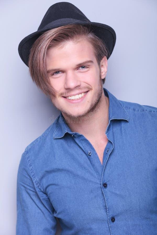 Lyckliga bärande hattleenden för ung man royaltyfri fotografi