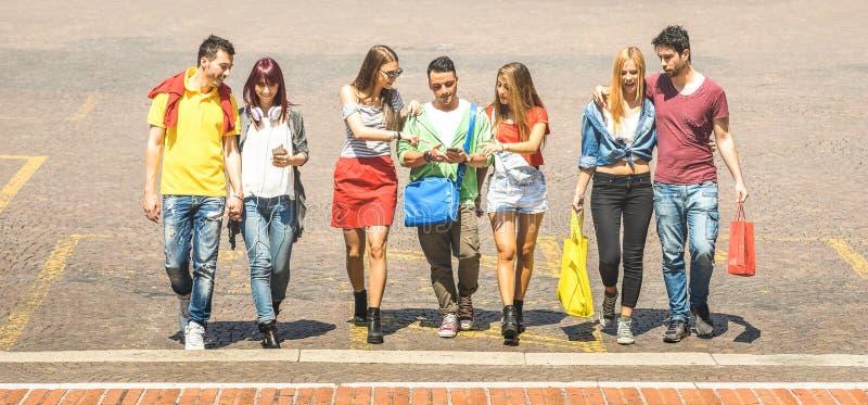 Lyckliga bästa vän som går och talar i centrum - turist- millennial grabbar och flickor ha gyckel runt om stadgator - royaltyfri bild
