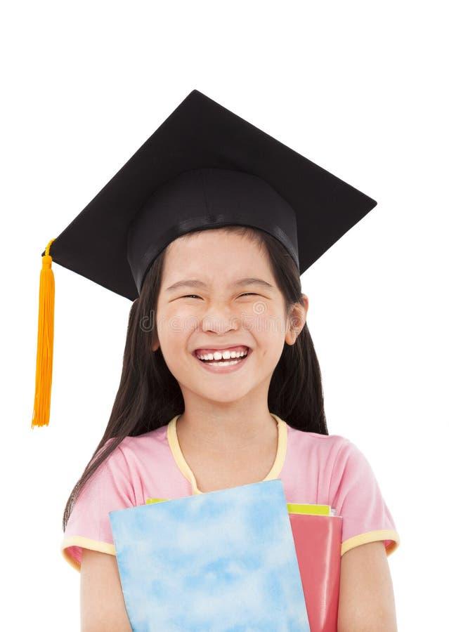 Lyckliga böcker för liten flickaavläggande av exameninnehav fotografering för bildbyråer