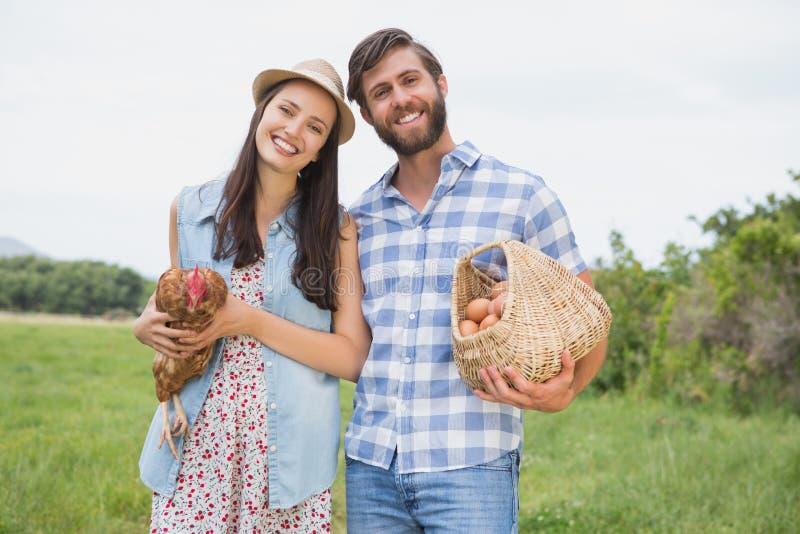Lyckliga bönder som rymmer höna och ägg arkivfoton