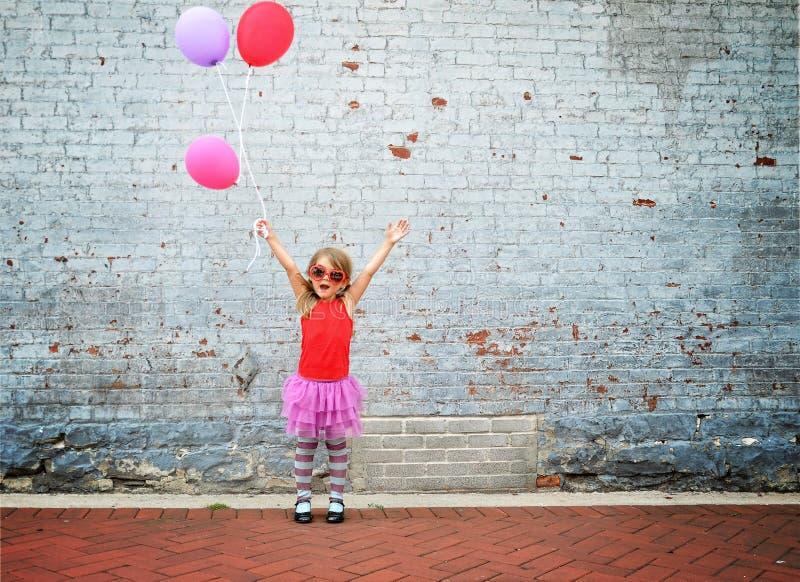 Lyckliga ballonger för barninnehavparti royaltyfria bilder