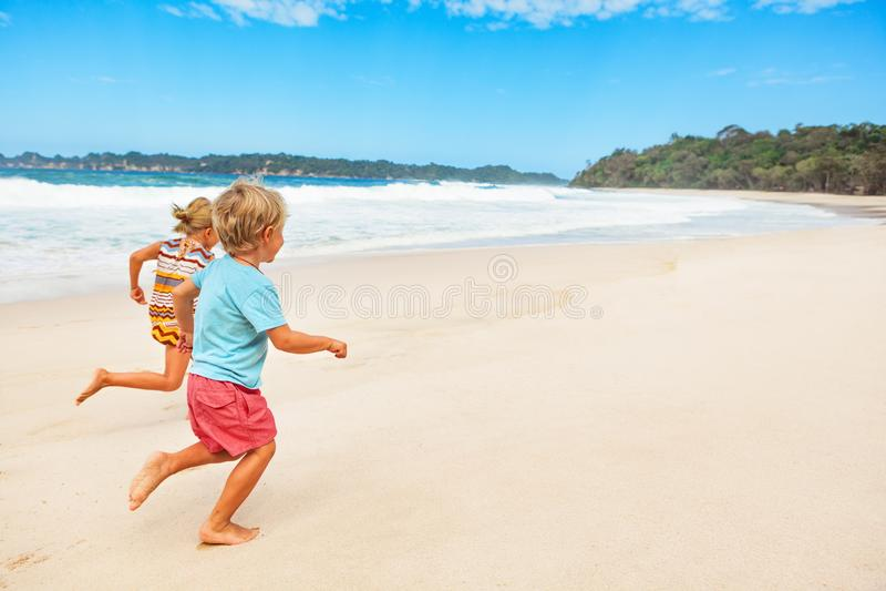 Lyckliga barfota ungar som kör med gyckel på stranden, går arkivfoton