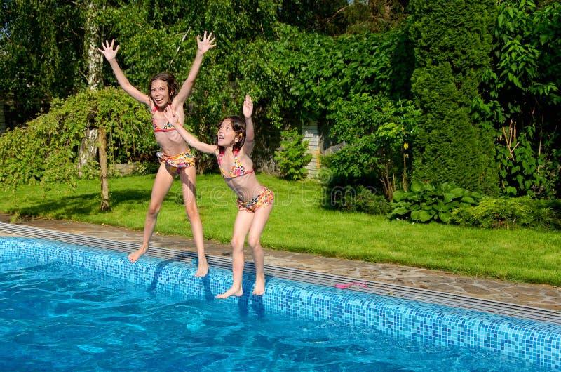 Lyckliga barn hoppar till simbassängen royaltyfri foto