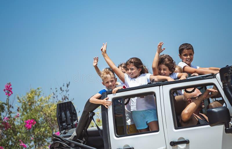 Lyckliga barn i bilen fotografering för bildbyråer