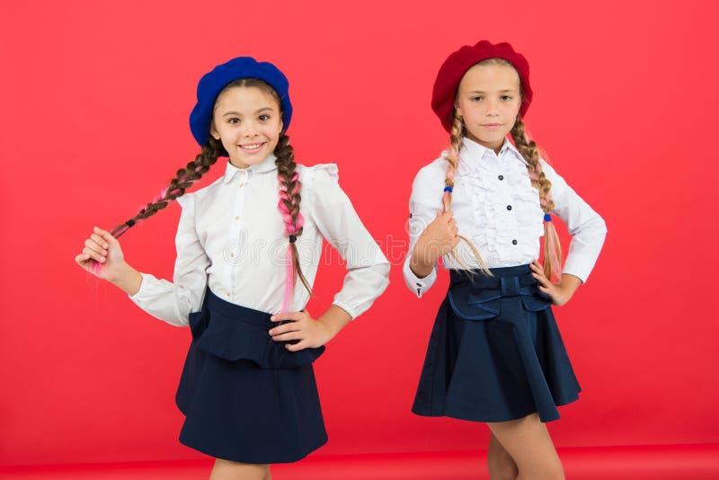 Lyckliga barn i likformig små flickor i fransk basker Utbildning utomlands ungemode kamratskap och systerskap b?st arkivfoto