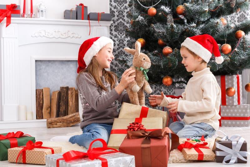 Lyckliga barn i santa hattar som packar upp julgåvor fotografering för bildbyråer