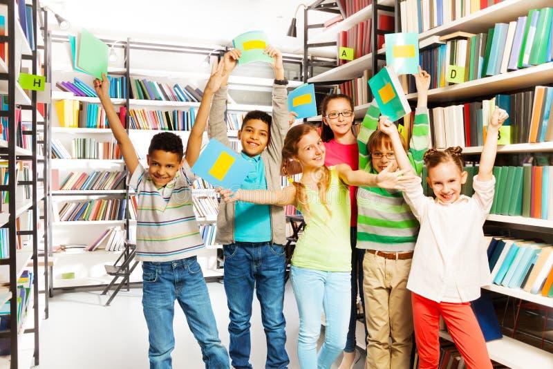 Lyckliga barn med händer rymmer upp skrivböcker royaltyfri foto