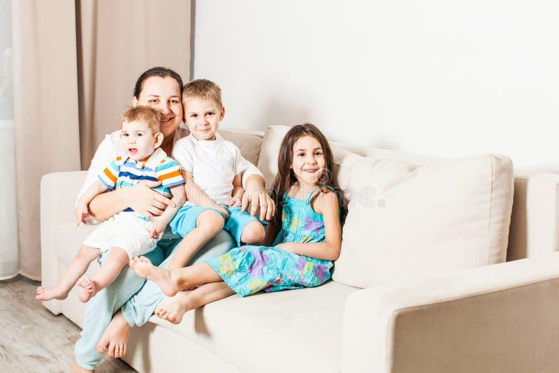 Lyckliga barn med mamman sitter på soffan royaltyfria bilder