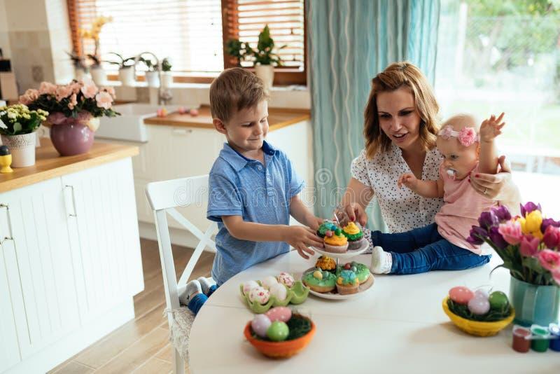 Lyckliga barn med modern som äter muffin royaltyfri bild