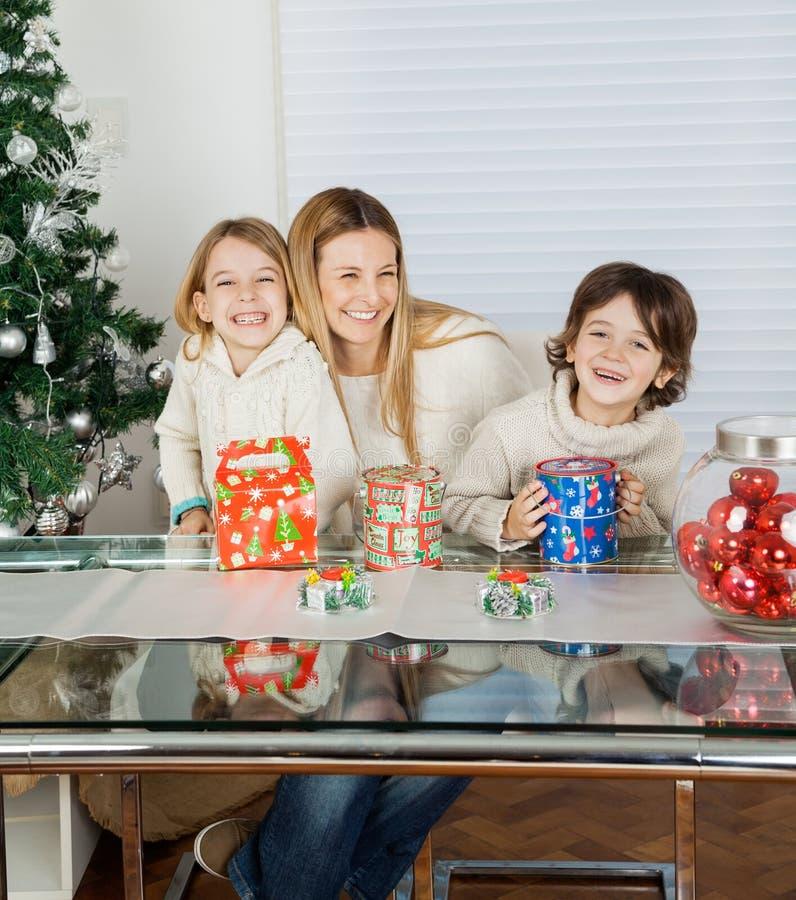 Lyckliga barn och moder med julklappar arkivbild