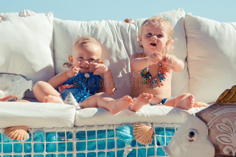 Lyckliga barn på bakgrunden av havet Roliga ungar som utomhus spelar Resa resväskan med seascapeinsida arkivfoton