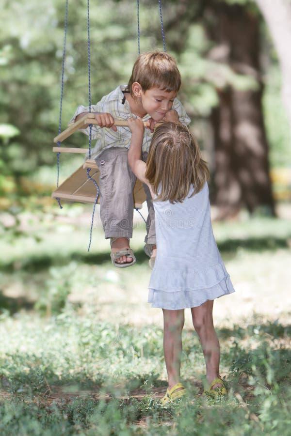 Lyckliga barn på swing på naturlig bakgrund arkivfoto