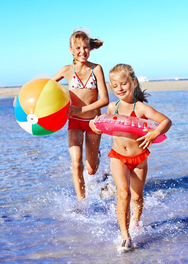 Barn som är rinnande på strand. arkivbilder