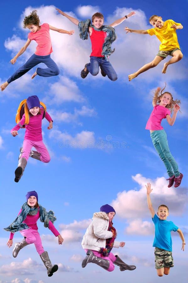Lyckliga barn som övar och hoppar i den blåa himlen royaltyfri foto