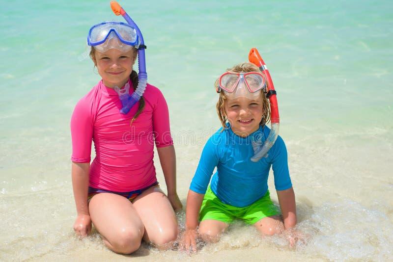 Lyckliga barn som bär snorkla kugghjulet på stranden arkivfoton