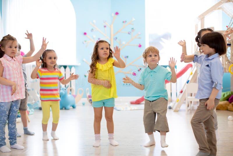 Lyckliga barn som har gyckel som inomhus dansar i ett soligt rum på daycare- eller underhållningmitten arkivbild
