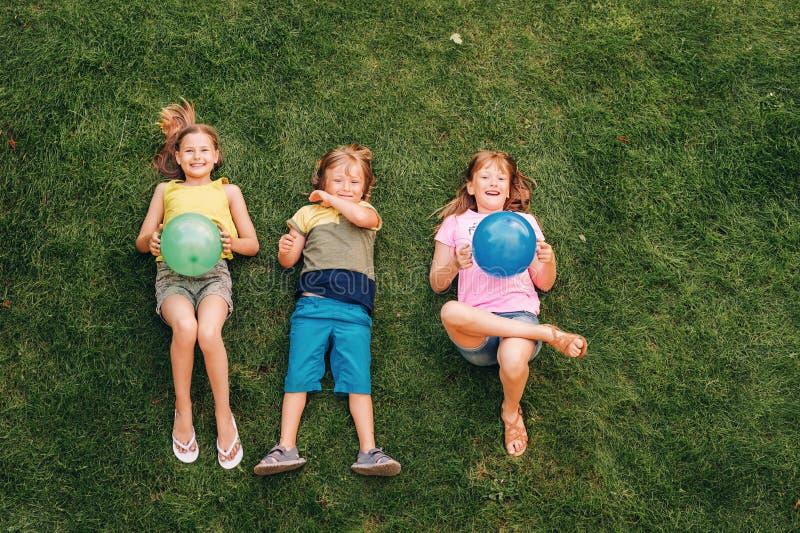 Lyckliga barn som har roligt utomhus arkivbilder