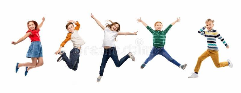 Lyckliga barn som hoppar ?ver vit bakgrund royaltyfria foton