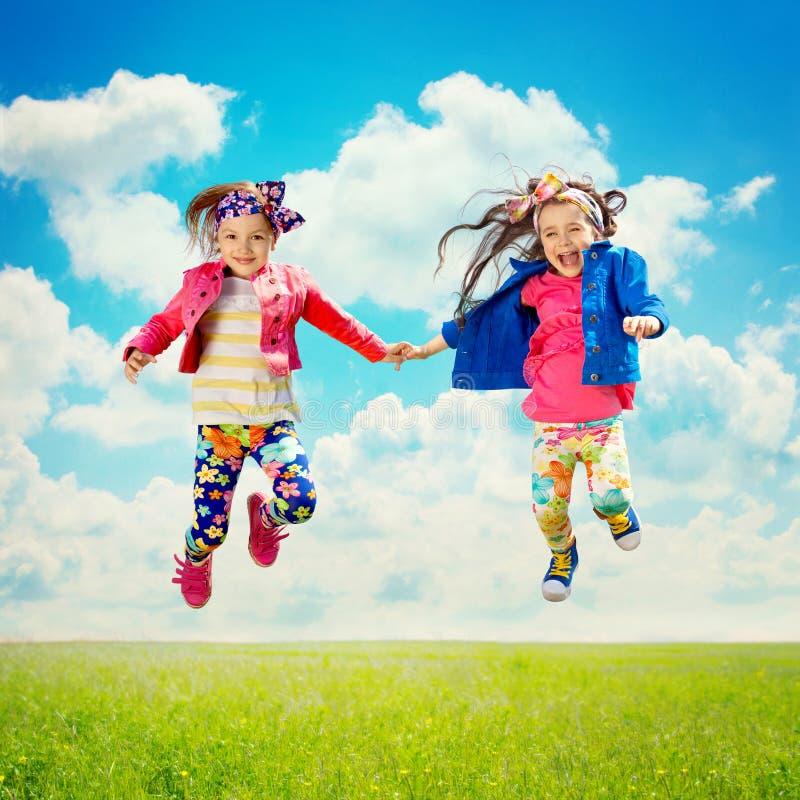 Lyckliga barn som hoppar på vårfältet arkivfoto
