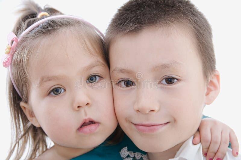 Lyckliga barn som isoleras på vit bakgrund Pojke- och flickaportra royaltyfria bilder