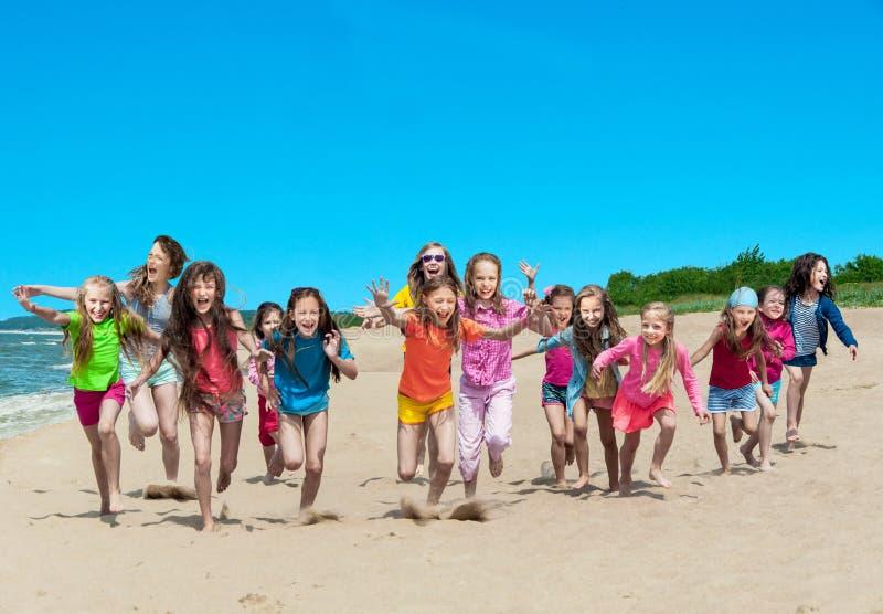 Lyckliga barn som kör på stranden arkivfoton