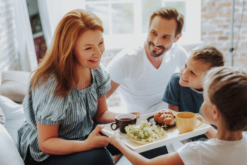 Lyckliga barn som kommer med frukosten till föräldrar i säng arkivbild