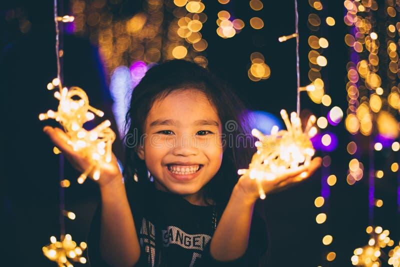 Lyckliga barn som rymmer ett ljus på en helgdagsafton för ` s för nytt år Gatanatt arkivfoton