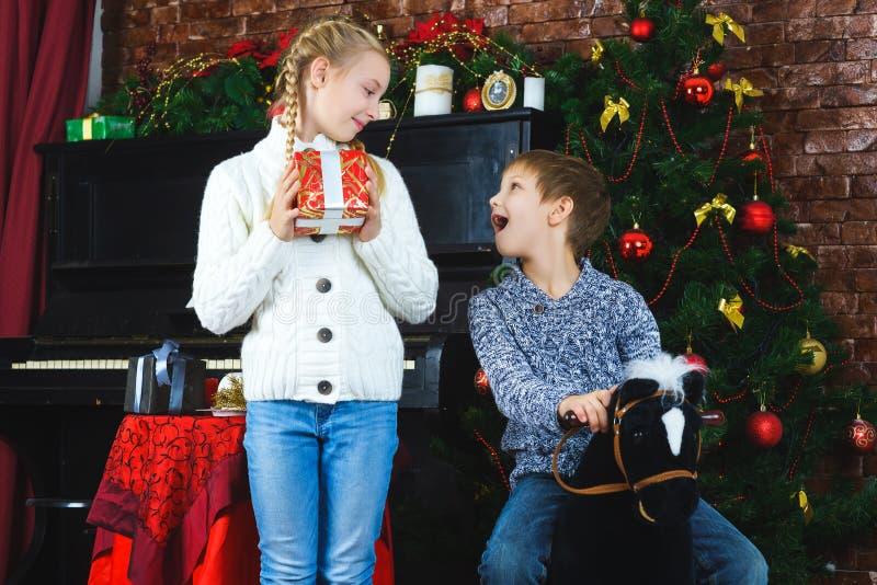 Lyckliga barn som rymmer gåvor Vänta på arkivbild