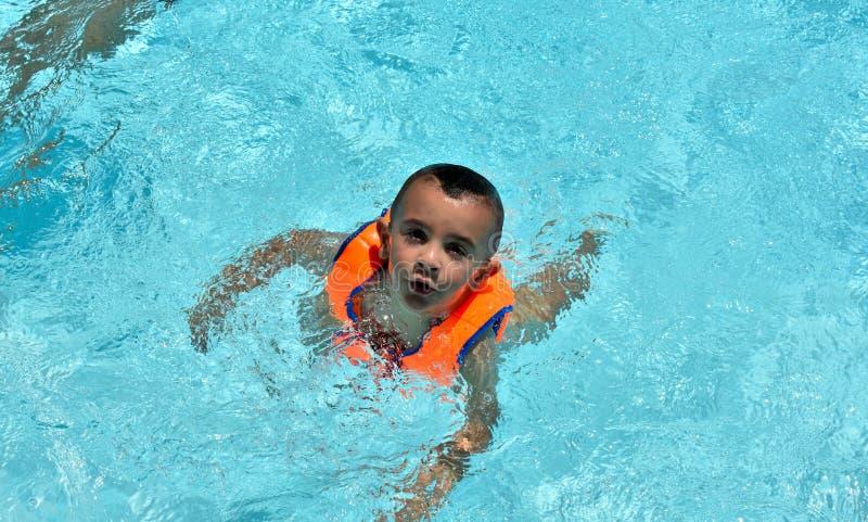 Lyckliga barn som simmar i p?len arkivbild