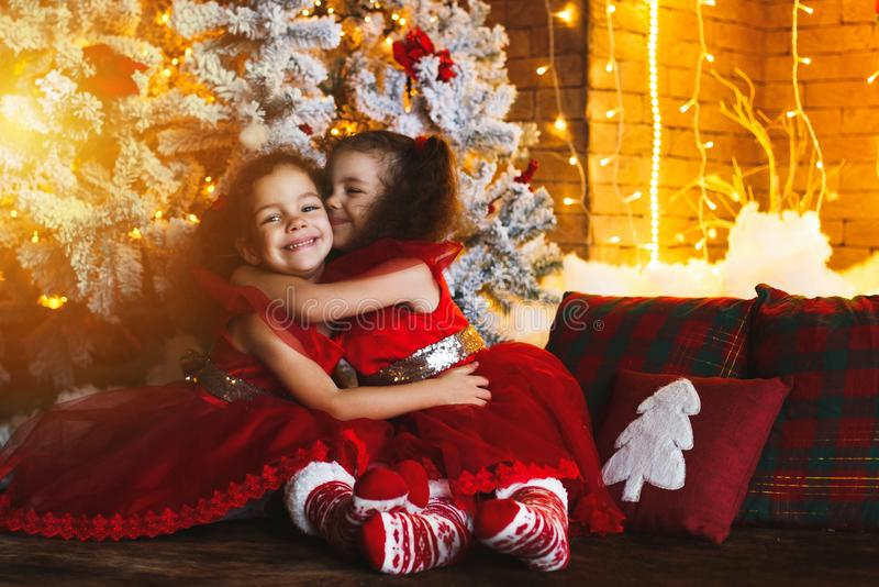 Lyckliga barn som sitter på golvet nära en julgran och ett a royaltyfria bilder