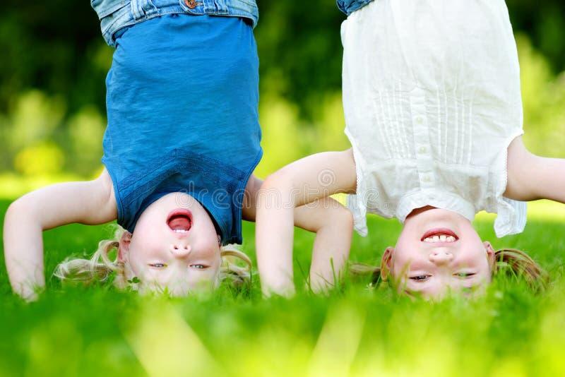 Lyckliga barn som spelar huvudet över häl på grönt gräs arkivfoton