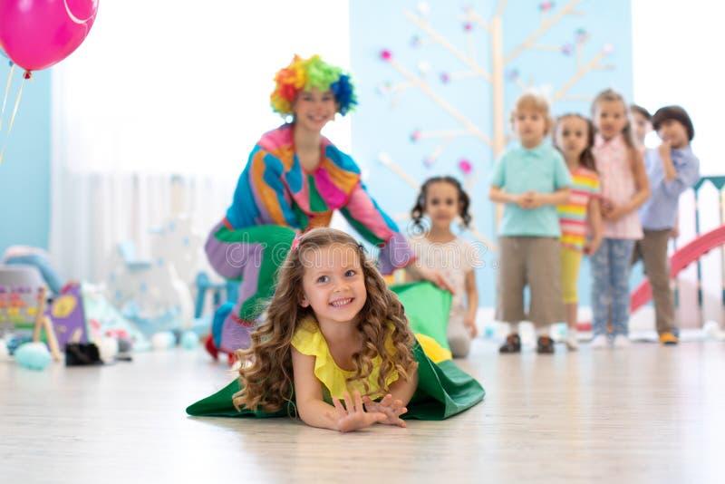 Lyckliga barn som spelar i barns lekrum för mitt för födelsedagparti eller underhållning Lurar nöjesfältet och lek royaltyfri fotografi